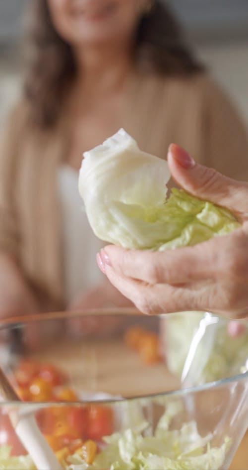 Elderly Women Talking while Making Salad in the Kitchen