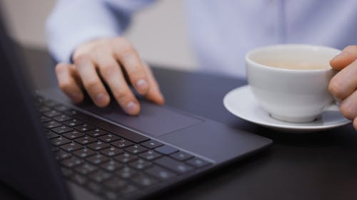 Person Using Laptop and Drinking Coffee