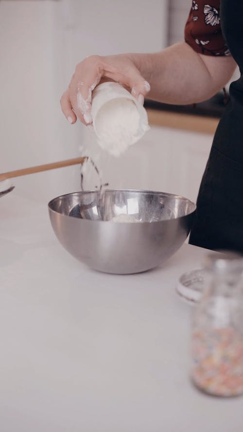 Person Pouring Flour on a Mixing Bowl
