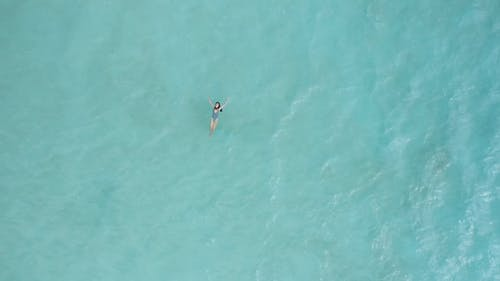 Aerial Shot of a Woman Swimming in the Ocean