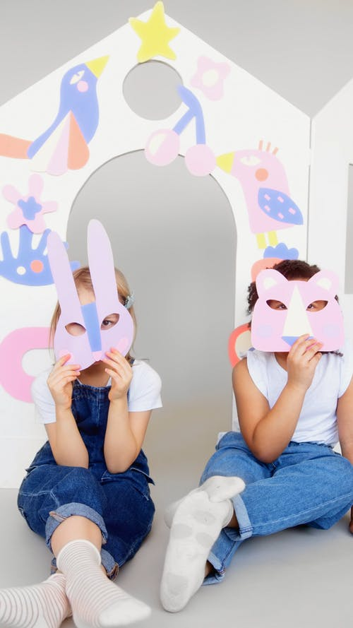 Two Kids  Covering Their Faces With Animal Masks
