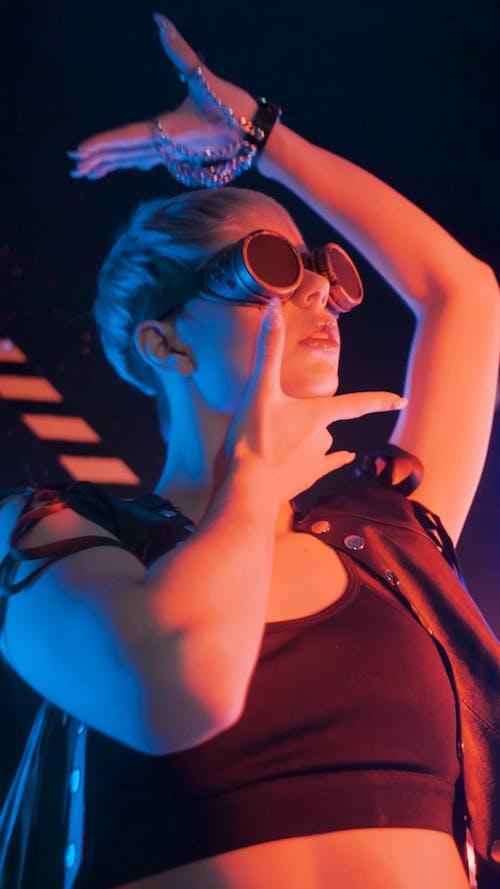A Stylish Woman Dancing Wearing Round Sun Glass