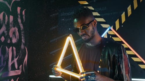 Man Wearing Cyberpunk Outfit Holding Triangle Shaped Neon Light