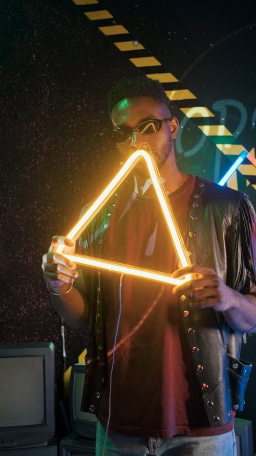 A Man Holding a Triangle Neon Signage