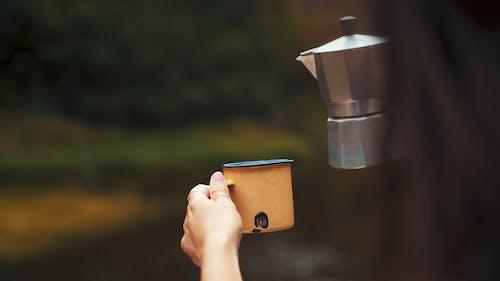 A Person Pouring Coffee To a Mug
