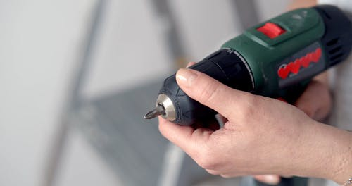 A Person Loading an Electric Drill