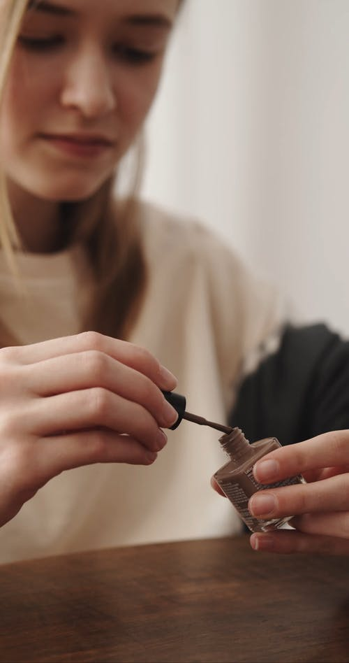 A Woman Holding a Nail Polish