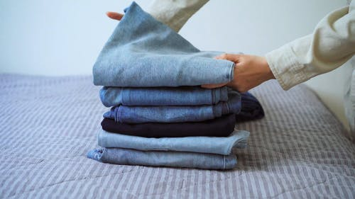 A Person Folding Denim Jeans