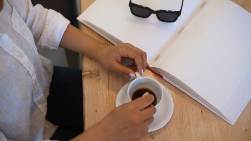 A Person Stirring a Cup of Coffee