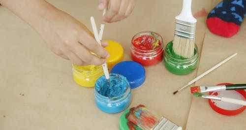 Kids Wetting Brushes In Paint