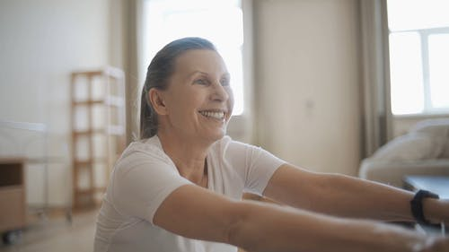 Elderly Woman Exercising at Home with Partner