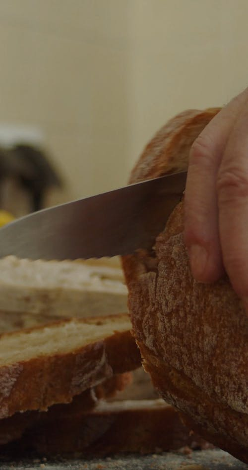 Close-up Video of A Person Slicing a Bread