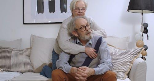 Elderly Couple Cuddling on a Sofa