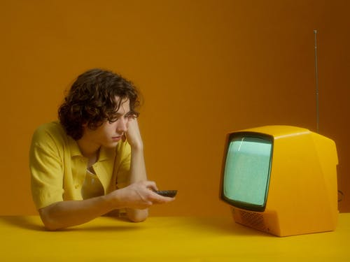 A Young Man Using The TV Remote Control