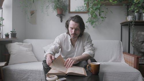 Man Sitting on Sofa Reading a Book