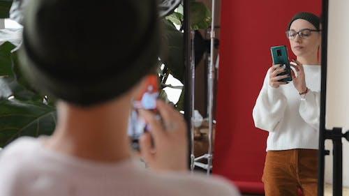 A Woman Taking A Selfie Through A Mirror