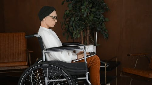Person Sitting on a Wheelchair While Using a Laptop