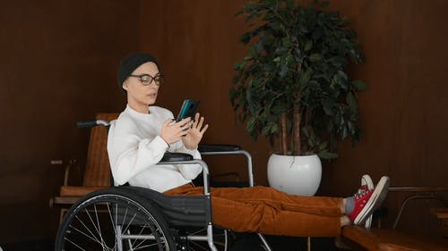Person Sitting in a Wheelchair While Using a Smartphone