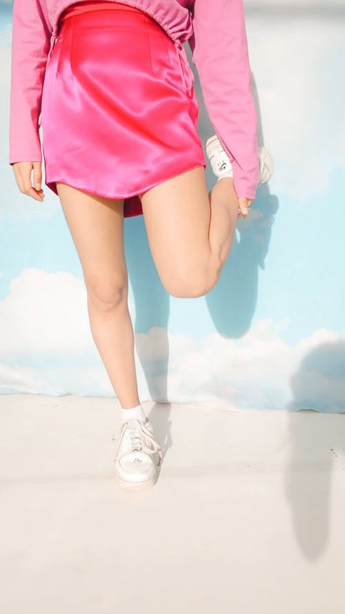 Person Wearing Pink Skirt and White Shoes
