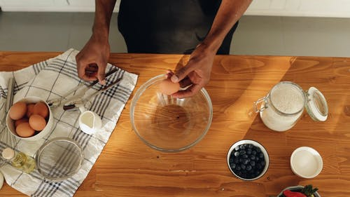 A Man Putting an Egg in a Mixing Bowl