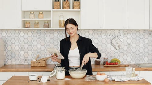Woman Looking at a Cookbook while Whisking the Flour in a Mixing Bowl