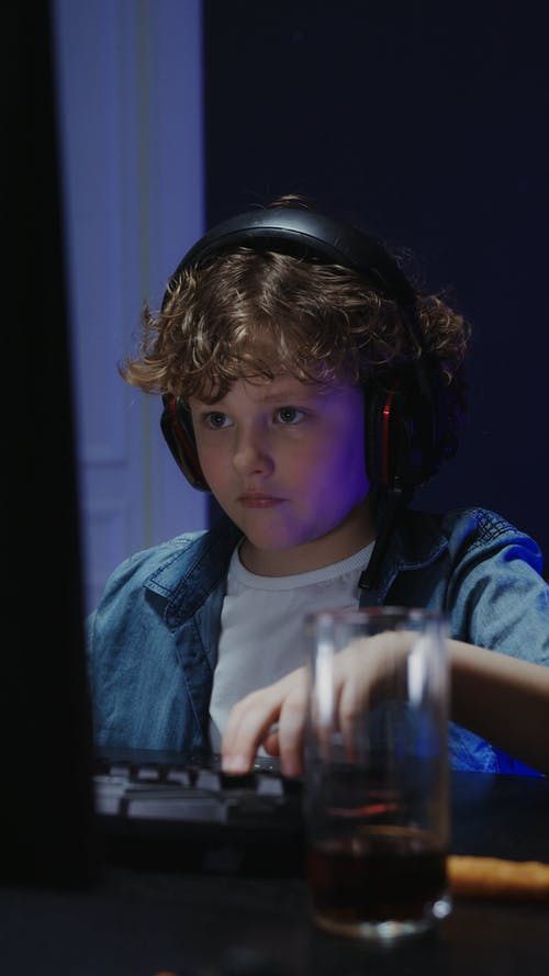 A Boy Eating Chips While Using Computer