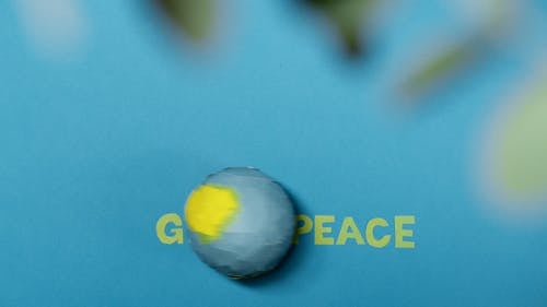 A Globe Rolling on a Blue Surface