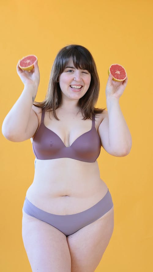 Plus Size Woman in Underwear Posing while Holding Grapefruit Slices