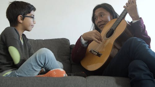 Man Teaching his Son How to Play Guitar