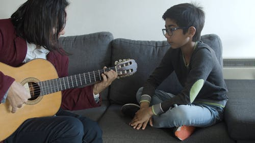Man Showing his Son How to Play Guitar