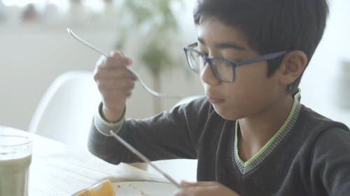 Video of a Boy Eating on Table