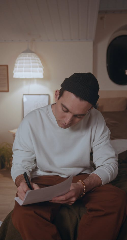 Man Writing Song in Bedroom