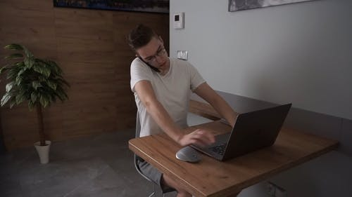 Man Talking on the Mobile Phone while Typing on his Laptop