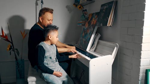 Dad Teaching His Child on How to Play the Piano