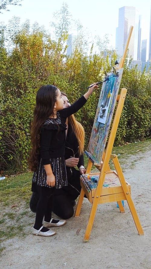 A Mother and Daughter Painting Outdoors