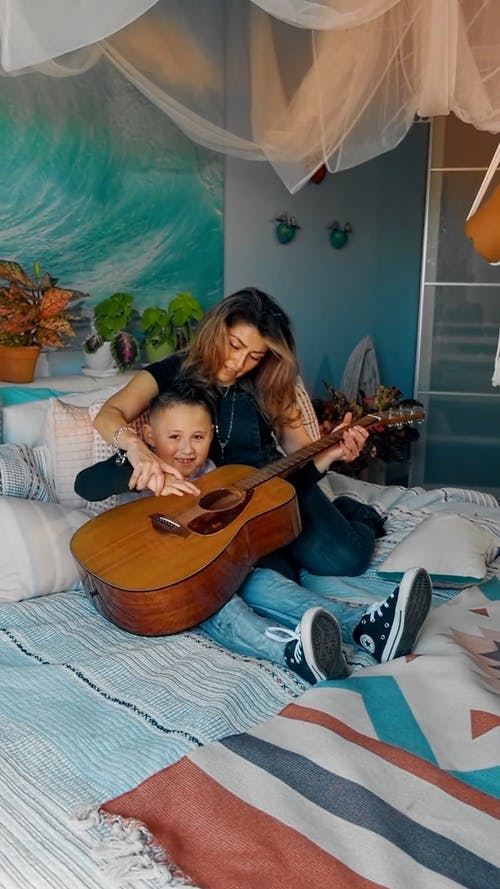 A Mother Teaching Her Son How to Play the Guitar