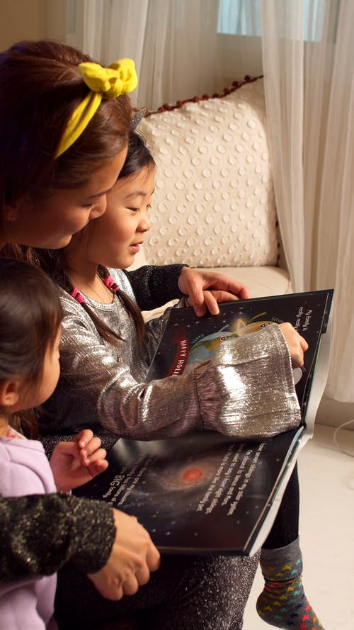 A Mother Reading a Story Book with Her Daughters