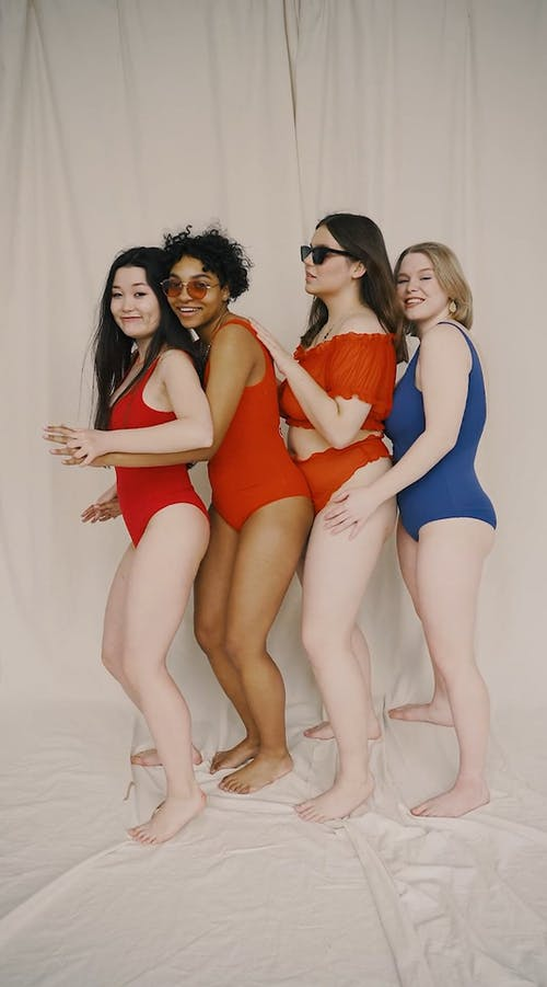 Women Dancing and Posing for the Camera While Wearing Bikinis