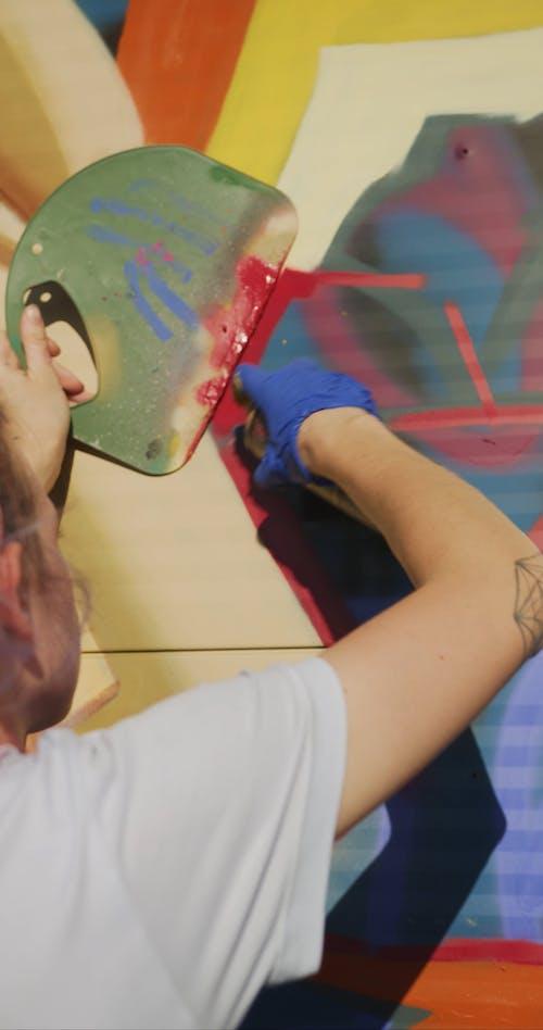 Woman Making Aerosol Art in Street
