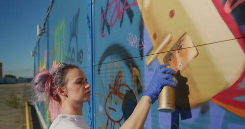 Video of a Woman Using Spray Can in Painting