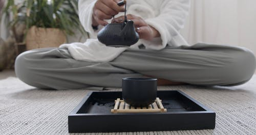 Person Putting Tea in Tea Cup