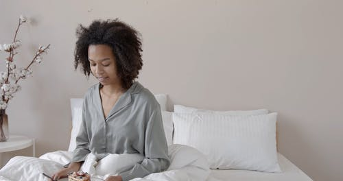 Woman Eating Cake at the Bed