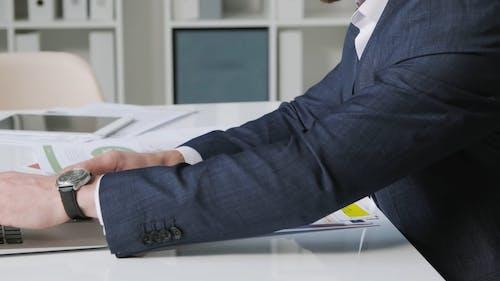 A Man Using Laptop while Sitting