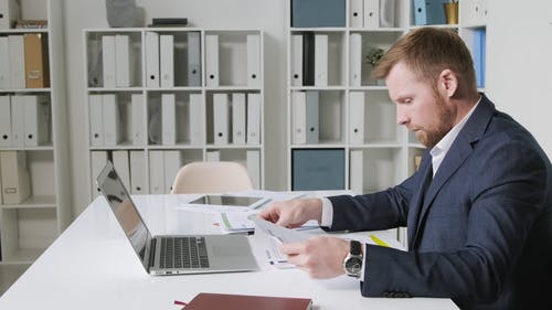 A Man Looking at Documents and Using His Laptop