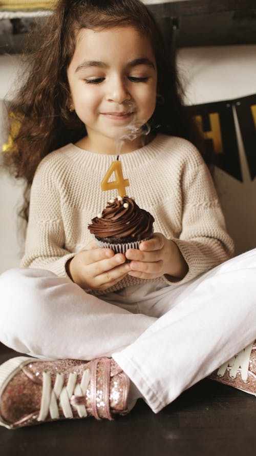 A Little Girl Blowing a Number Four Candle on a Cupcake
