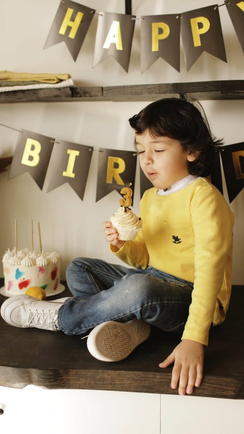 Boy Blowing the Lighted Candle on Cupcake