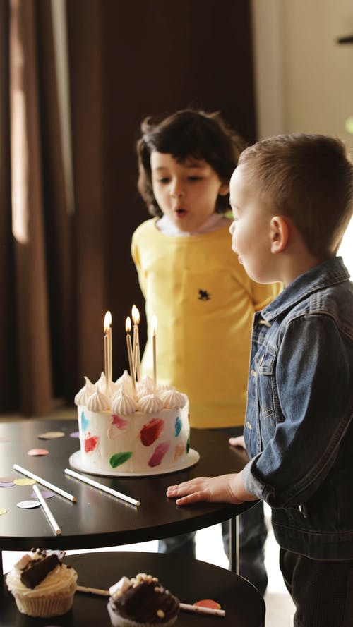 Boys Blowing the Lighted Candles on a Birthday Cake
