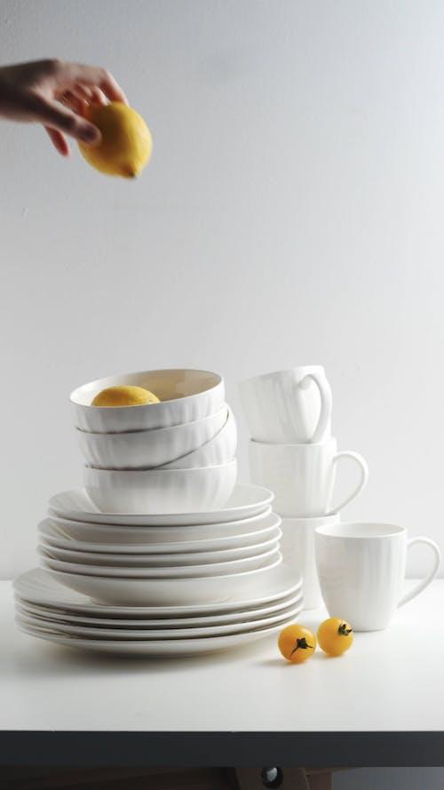 A person Putting Lemon Inside a Bowl