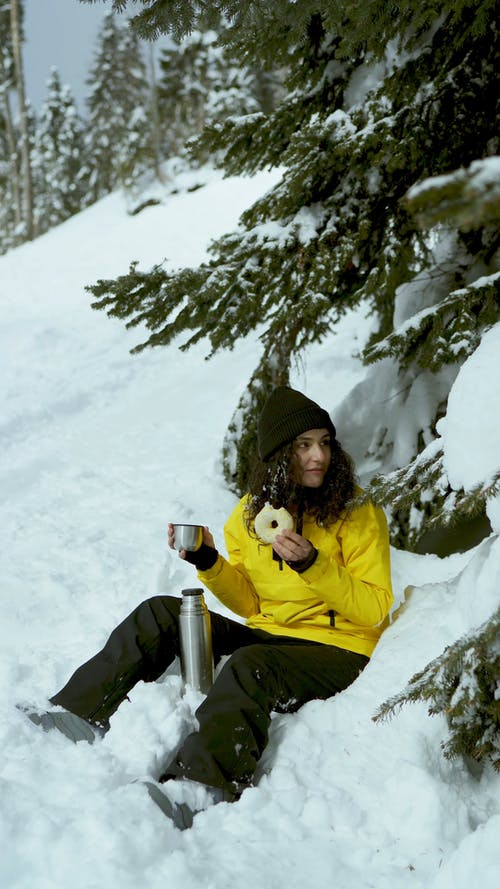 Woman Eating Donut and Drinking Coffee in Snow