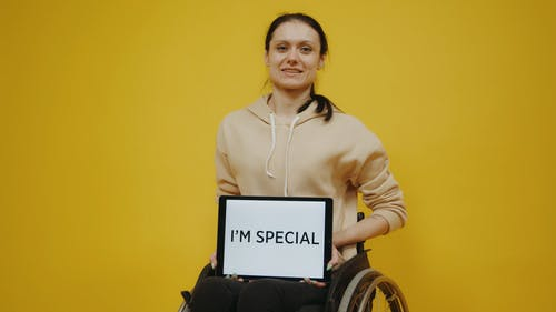 Woman in Wheelchair Holding a Tablet